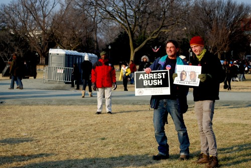 "Father and son duo carry signs around D.C. stating ""Arrest Bush."""